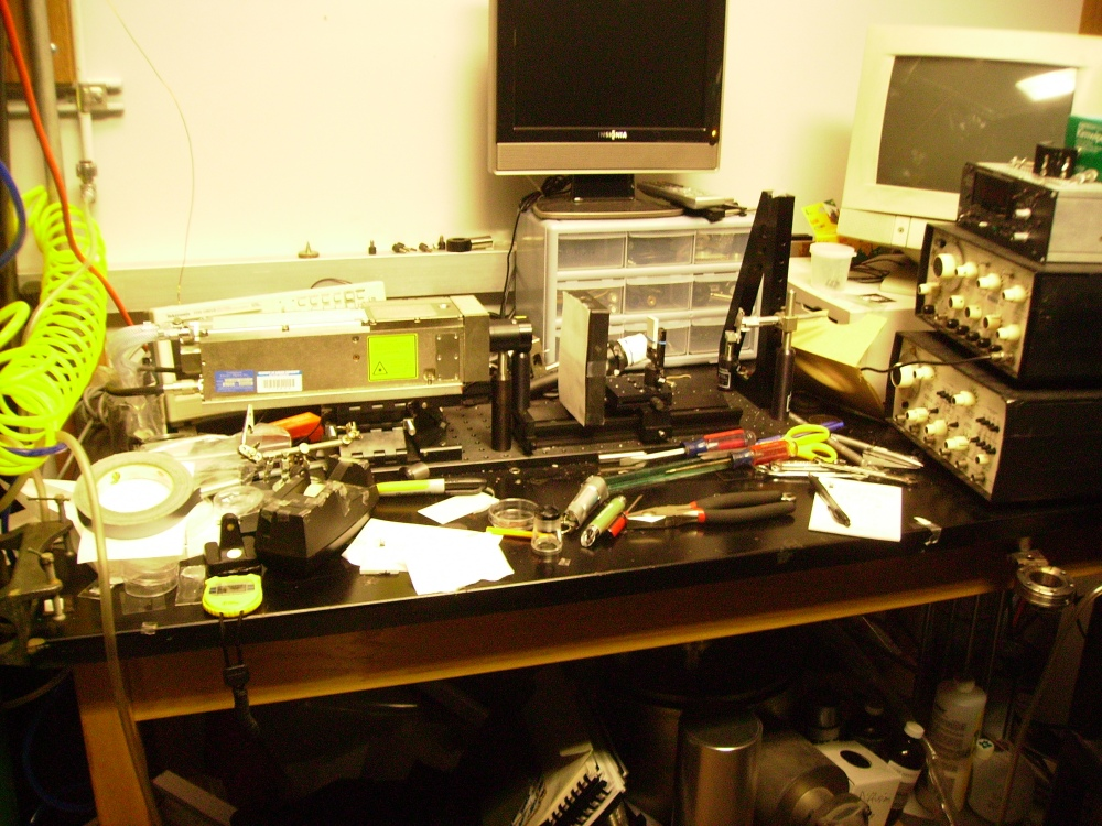 Tanya Mikulas plays with lasers on a cluttered lab bench. Laser ablation to create a prototype of a novel boron nitride contact mask,, Tanya Mikulas, 2010