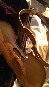 Smashed viola in a pile of other smashed stringed instruments. Photo by Tanya Mikulas
